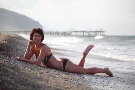 A beautiful woman is basking in the sun in the sea. Young woman sitting on the beach. Beautiful adult woman sunbathing on the beach.