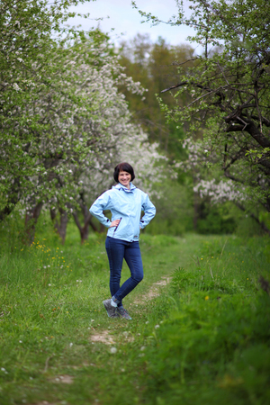 Beautiful mature woman posing for the camera in the spring garden. The girl enjoys the flowering of apple trees.