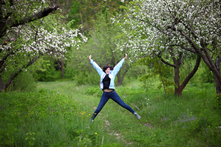 Beautiful woman in the spring garden. The girl enjoys the flowering of apple trees.