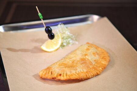 Original serving of meat pie in a restaurant. Belyash with meat. Argentinian empanada. Tatar meat pie with ground beef.