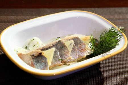 Marinated herring fillets with red onion, dill and spices on white plate. Herring fillet with onion lemon and dill.