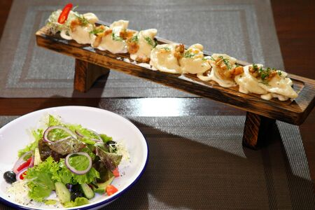 Dumplings with cream on a wooden board and salad. Dumplings with potatoes and salad.