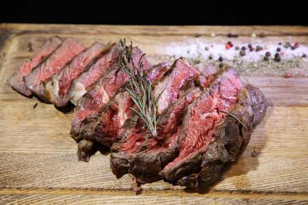 Medium-roasted steak cut into pieces on a wooden board with sauce and seasonings. Delicious steak. Beef steak medium rare on vegetable cushion. Beef steak on wooden plate.