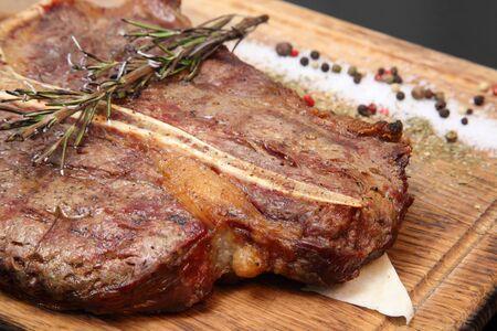 Bistecca di media arrosto tagliata a pezzi su una tavola di legno con salsa e condimenti. Bistecca deliziosa. Bistecca di manzo mediamente cotta su cuscino di verdure. Bistecca di manzo sul piatto di legno.