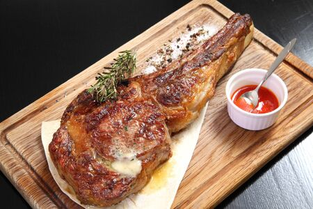 Steak Tomahawk roast on a wooden board with sauce and salt.