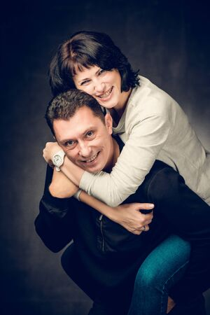 Playful mature married couple photographed in the studio. Handsome man in jeans and smiling woman in shirt playing. Фото со стока
