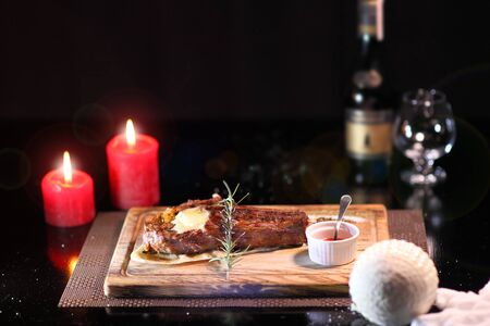 Rib eye steak on the New Years table. Steak rib eye roast on a wooden board with sauce and salt. Beef steak on wooden plate. Фото со стока