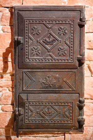 Wrought iron door of the stove with a national Ukrainian ornament. Iron door of the stove. Two old furnace doors. Ancient stove. Cast iron door for furnaces. Iron door ornament.