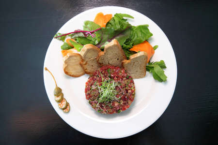 Raw tartar meat with spices, croutons and herbs. Beef tartar with capers. Beef tartar with slices of bread. Raw meat tartare for gourmet meat. Banque d'images