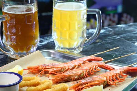 Beer pub. Langoustines and beer. Beer and seafood snacks. Langoustines, beer, squid rings. Фото со стока - 152399182