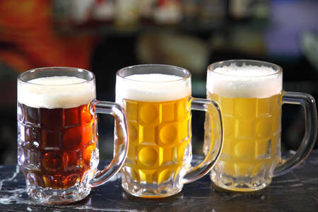 Glasses with different sorts of craft beer. Red, bronze and white beer in beer glasses on the bar. Glasses of light and dark beer on a pub background. Фото со стока