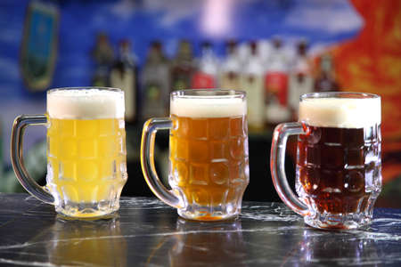 Glasses with different sorts of craft beer. Red, bronze and white beer in beer glasses on the bar. Glasses of light and dark beer on a pub background. Фото со стока - 154184735