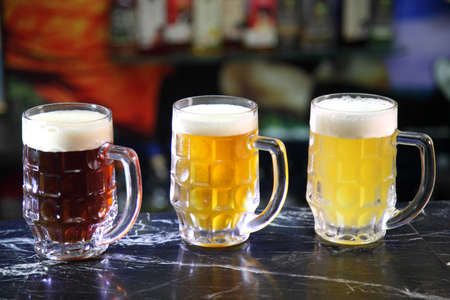 Glasses with different sorts of craft beer. Red, bronze and white beer in beer glasses on the bar. Glasses of light and dark beer on a pub background. Фото со стока - 154184737