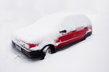 red car covered by snow