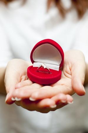 een afbeelding van een rood vak met verlovingsring binnen