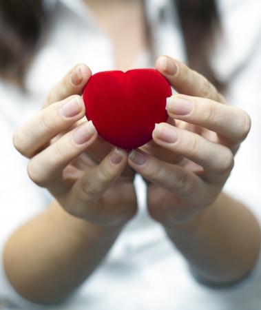 een afbeelding van rode engagement vak houden door hand van jonge meisje