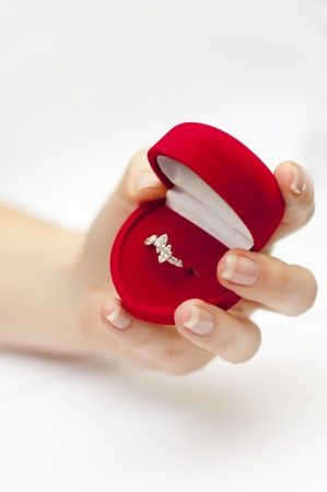 an image of red box with engagement ring inside held in hand photo