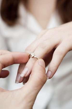 an image of situation of inserting engagement ring into a finger Foto de archivo