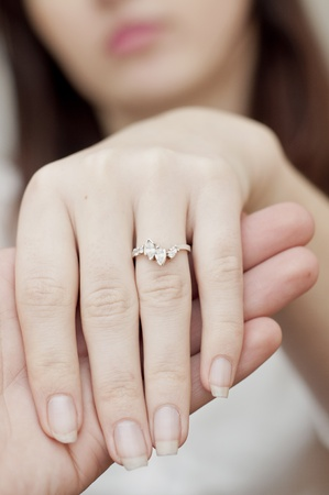 an image of engagement ring inserted into finger photo