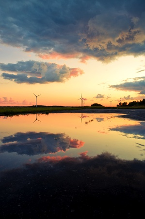 An image of wind turbines reflection in the water at the sunset photo