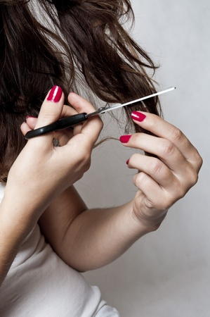 Attractive young woman is cutting her own hair photo