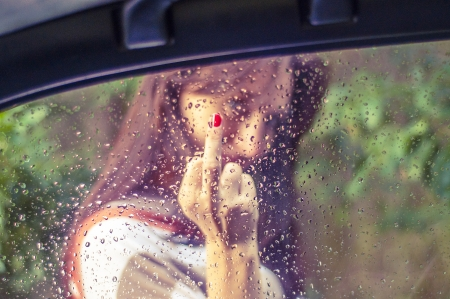 An image of girl showing her middle finger. Focus on the window Stock Photo - 16009753