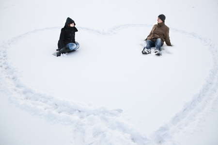 An image of cuple sittig on the snow