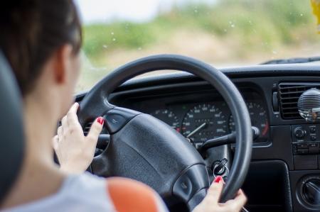Handen van een vrouwelijke bestuurder op het stuurwiel Stockfoto