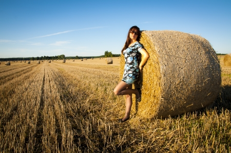 An image of brunette girl portrait and straw bale  photo