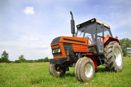 Red tractor on the meadow photo