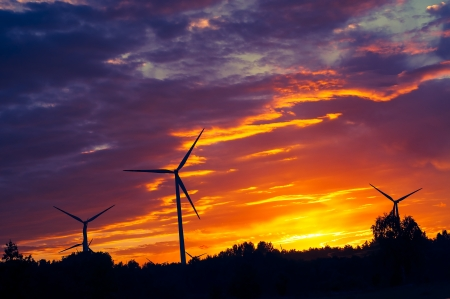 A silhouette of windturbines on a amazing sunset photo