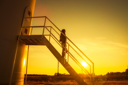 Girl standing on a stairs to windturbine during amazing sunset photo