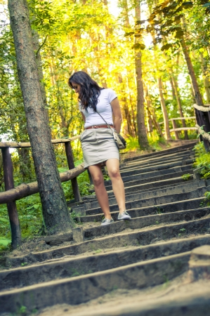 An image o girl walking through the forest pathway photo