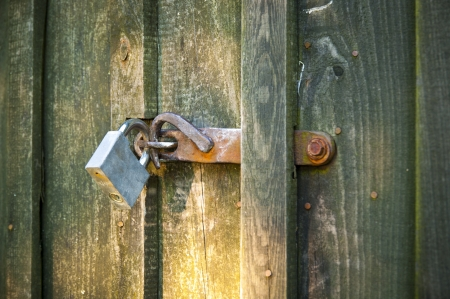An image of closed old wooden door with padlock photo