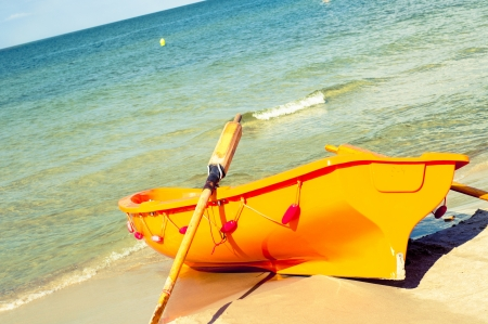 An image of orange rescue boat on the beach of baltic sea photo