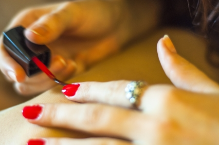 Girl paints her nail into red color. Shallow DOF Stock Photo - 16288897