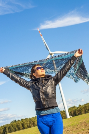 An image of girl holding canvas-cape and windturbine in background photo