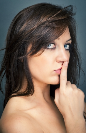 an image of portrait of a beautiful brunette with a finger on her lips showing to keep silence Stock Photo - 16378285