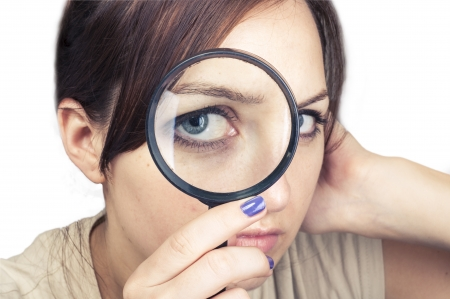 an image of girl with magnifying glass over her face photo