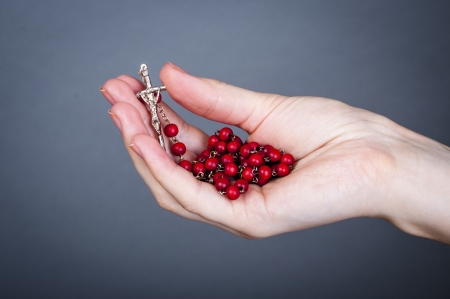 an image of rosary on female hand photo