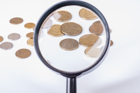 an image of coins lying on magnifying glass Stock Photo