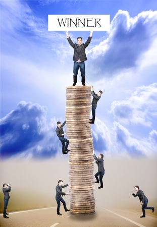 An image of businessmens climbing to tower made of coins Stock Photo