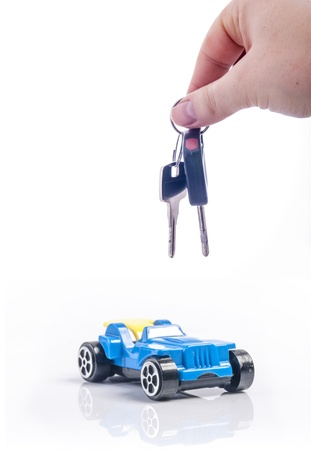 An image of keys above toy blue car photo