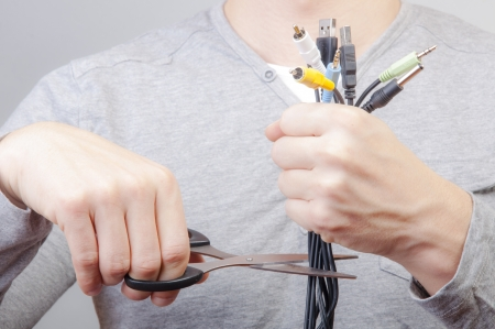 An image of man holding many cables with plug and scissors in other hand photo