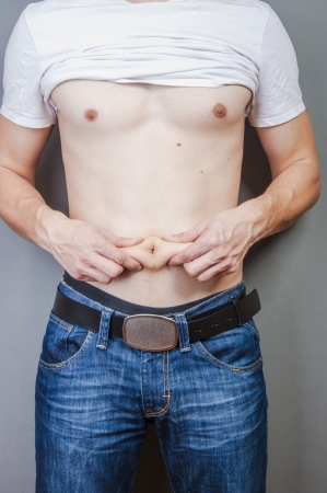 An image of man hold his fat on stomach photo