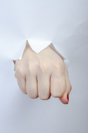 An image of fist punch through paper photo