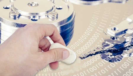 an image of hand with eraser removing data from hdd Stock Photo