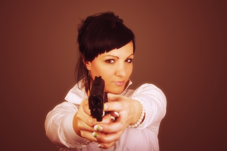 An image of elegant businesswoman with gun photo