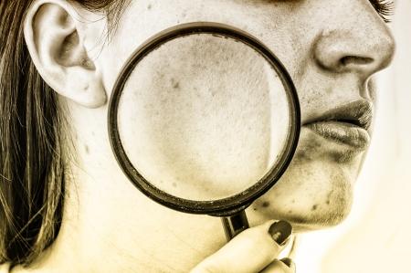 Een beeld van vrouwen met een huid probleem houdt vergrootglas over haar gezicht