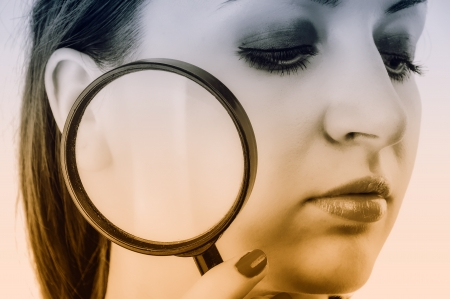 An image of women with skin problem holding magnifying glass over her face photo